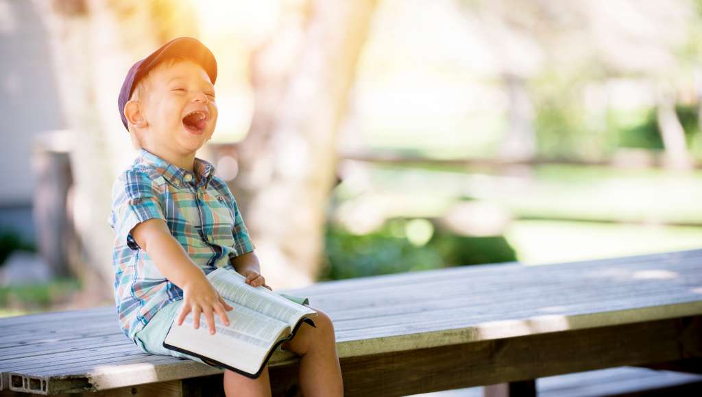 Small boy with Bible laughing