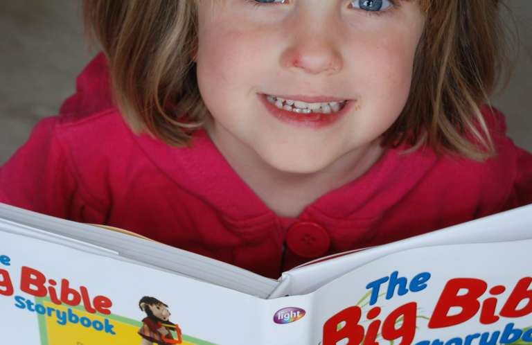 Girl with big bible storybook
