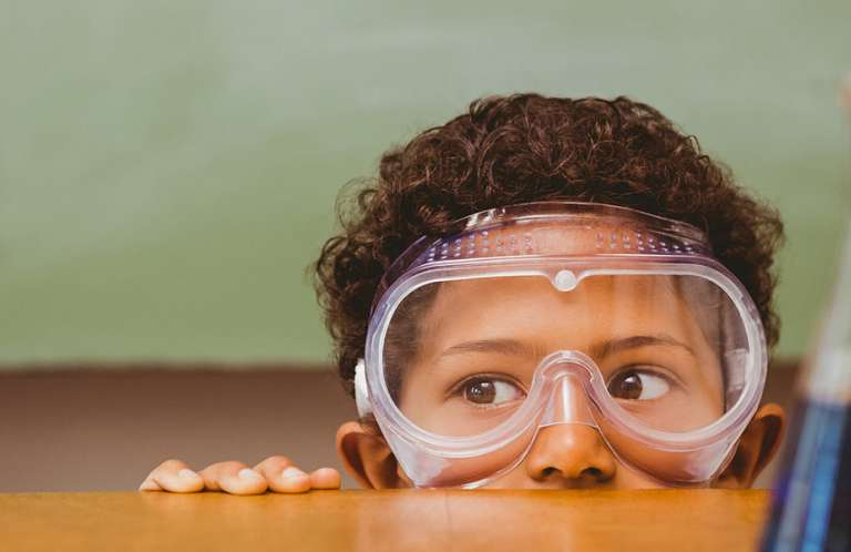 Boy in safety goggles with science equipment